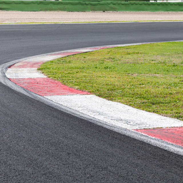 """""""Rough curb at right turn on motor sport track with green field a"""" stock image"""