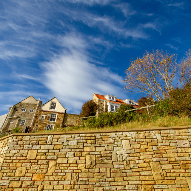 """""""Cottages above the sea wall, rear view. Robin Hoods Bay. External rear view on a sunny day."""" stock image"""