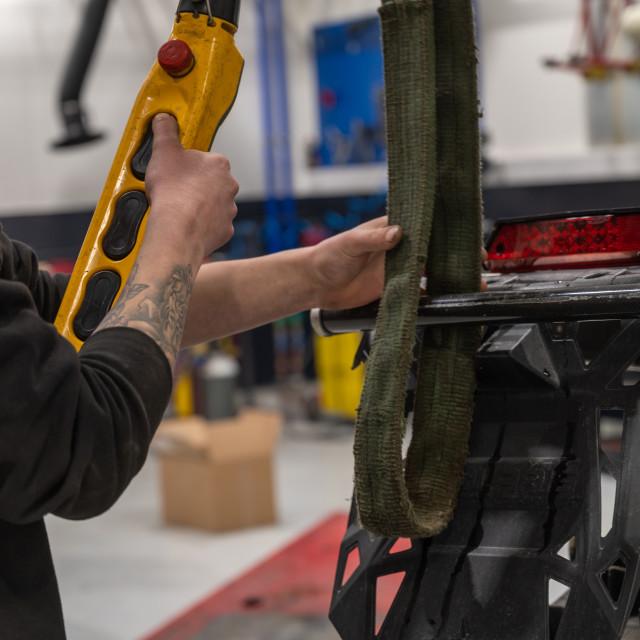 """Mechanic raising snowmobile"" stock image"