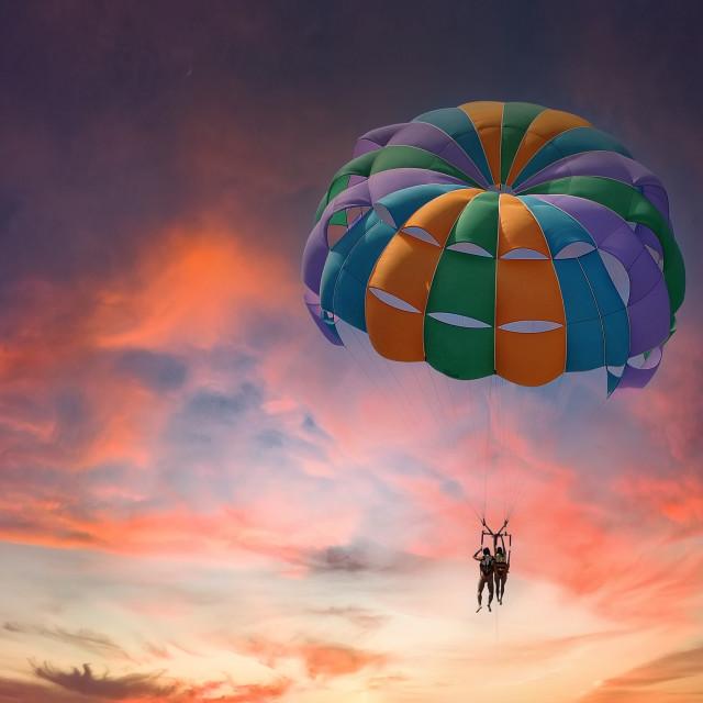 """Two people enjoy parasailing flight during sunset bright colorfu"" stock image"