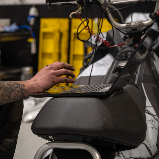 """Mechanic repairing a snowmobile"" stock image"