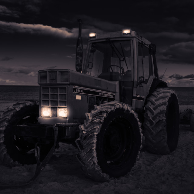 """Moody mono of old tractor on beach."" stock image"