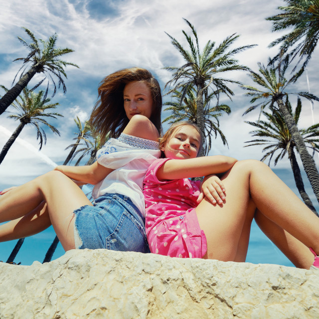 """""""Happy mother and 8s daughter sit under cloudy blue sky and palm"""" stock image"""