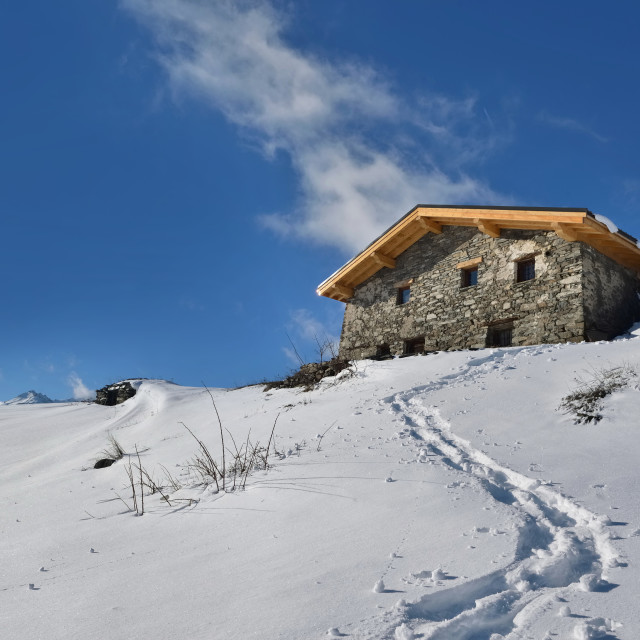 """""""traditional alpine chalet at the top of snowy mountain under blu"""" stock image"""