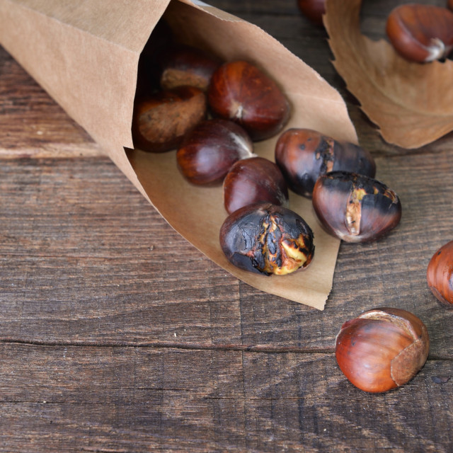 """""""roasted chestnuts in a papaer bag spilled on wooden table"""" stock image"""