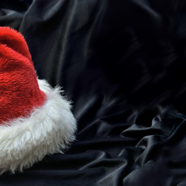 """""""red santa claus hat in black textile background"""" stock image"""