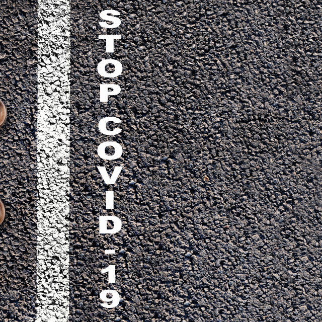 """""""top view on foot behind a line drawing on asphalt with text stop covid-19"""" stock image"""