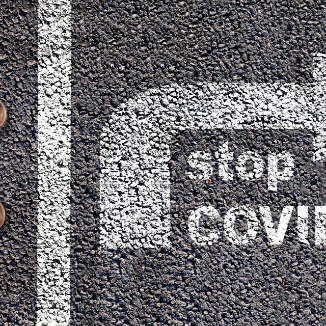 """""""top view onfoot behind a line drawing on asphalt and an arrow to the opposite with text stop covid-19"""" stock image"""