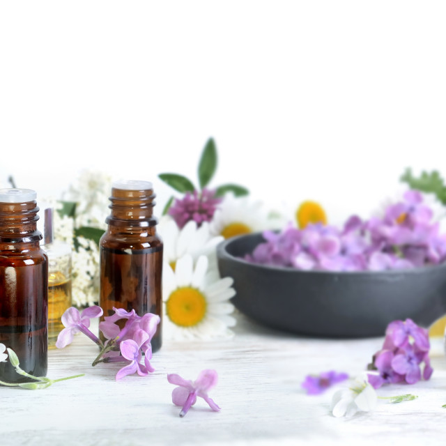 """""""few bottles of essential oil among petals of flowers on a table"""" stock image"""