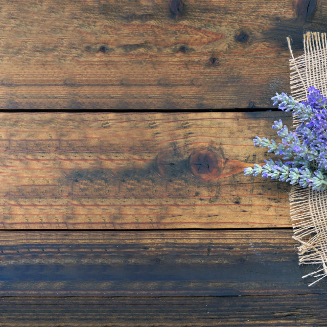 """""""bunch of lavender flowers next to a little basket full of petals on a natural fabric on wooden background"""" stock image"""