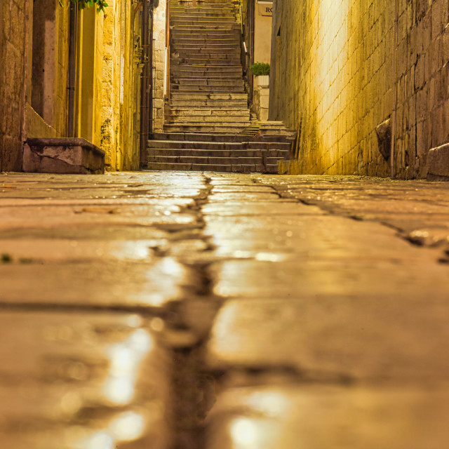 """""""Low Angle View of Cracked Cobblestones Leading to Stone Steps"""" stock image"""