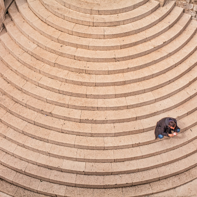 """""""High Angle View of Man Sitting on Curved Stone Steps"""" stock image"""
