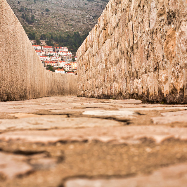 """""""Low Angle View of Thick Stone Wall Surrounding Old City of Dubrovnik"""" stock image"""