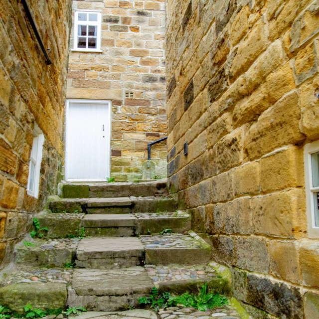 """""""Robin Hoods Bay, Yorkshire East Coast, England. Narrow Ginnel with Steps and Cobbles."""" stock image"""