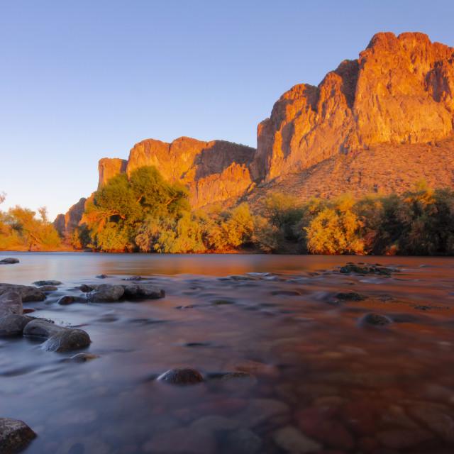 """Gentle rapids in front of brilliant orange mountains"" stock image"