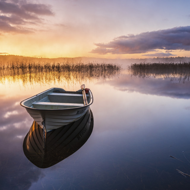 """Boat on still lake at sunrise"" stock image"