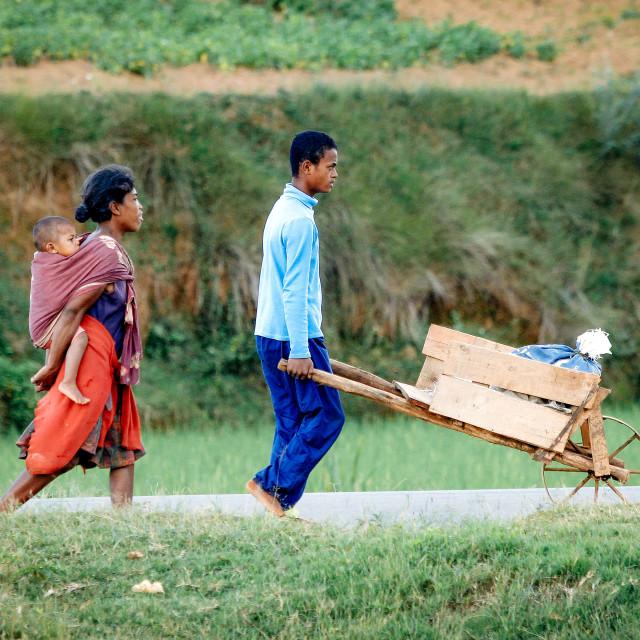 """poor family with wheelbarrow"" stock image"