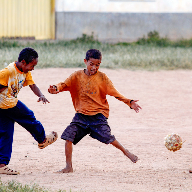 """boys playing football without shoes and self made ball"" stock image"