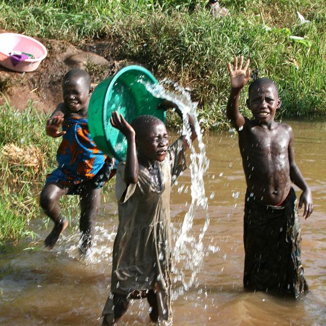 """Playing in the creek, Uganda, Africa"" stock image"