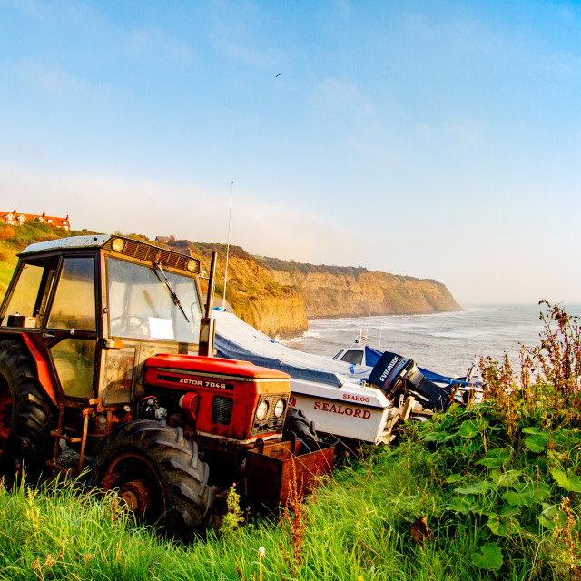 """""""Parked Zetor 7045 Red Tractor next to the Access to the Beach and Fishing Boats. Robin Hoods Bay, Yorkshire East Coast, England."""" stock image"""