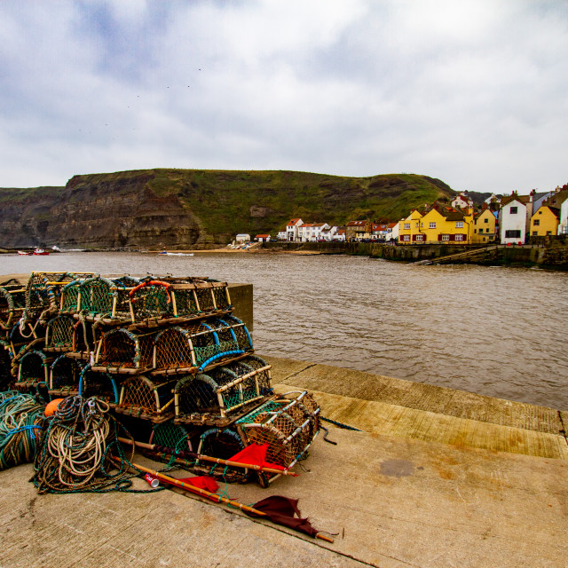 """View Across Staithes Harbour towards the small sandy beach and the Cod and Lobster Pub."" stock image"