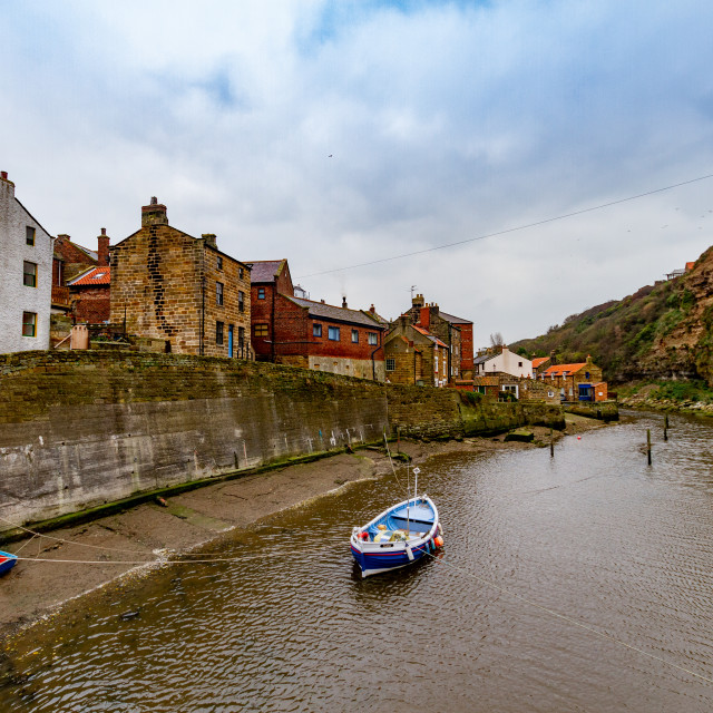 """Blue Fishing Cobble Moored in Staithes Beck, Retaining Wall and Cottages in the background."" stock image"