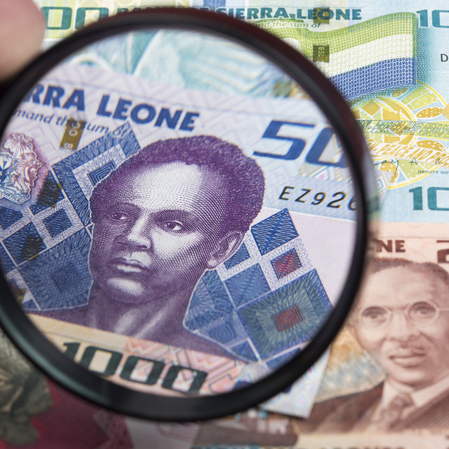 """Sierra Leonean money in a magnifying glass"" stock image"
