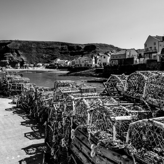 """Lobster Pots Stacked on North Side of Staithes Harbour, Yorkshire, England. (monochrome)"" stock image"