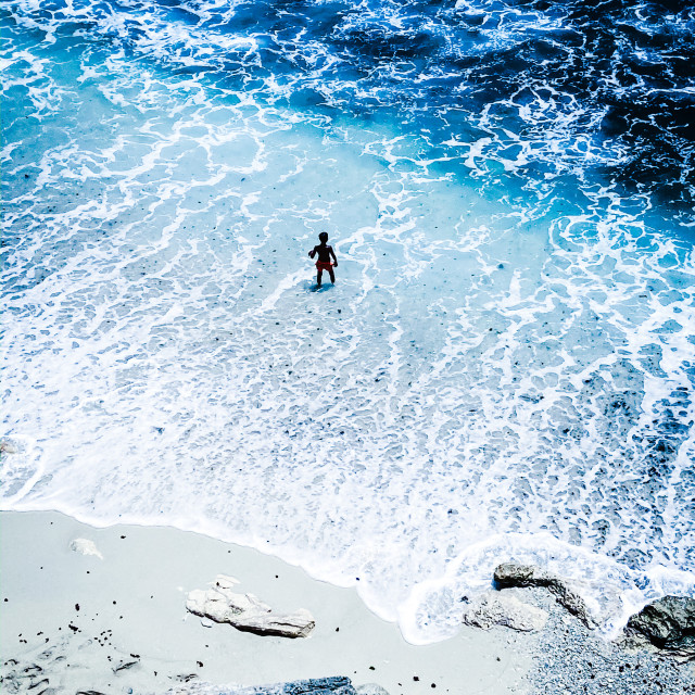 """A child plays by the waves on Dream Beach, on the island of Nusa Lembongan, Indonesia"" stock image"