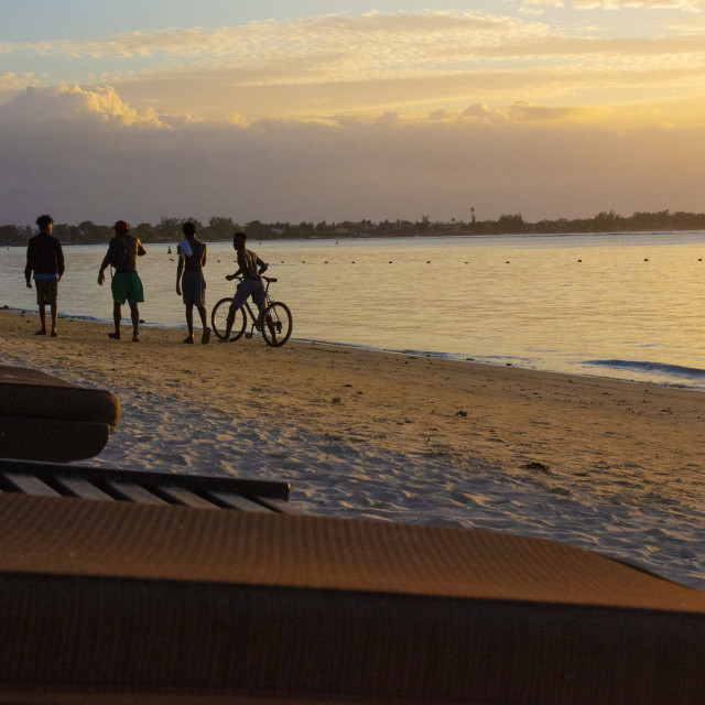 """Children playing at sunset on Mont Choisy Beach, Mauritius"" stock image"