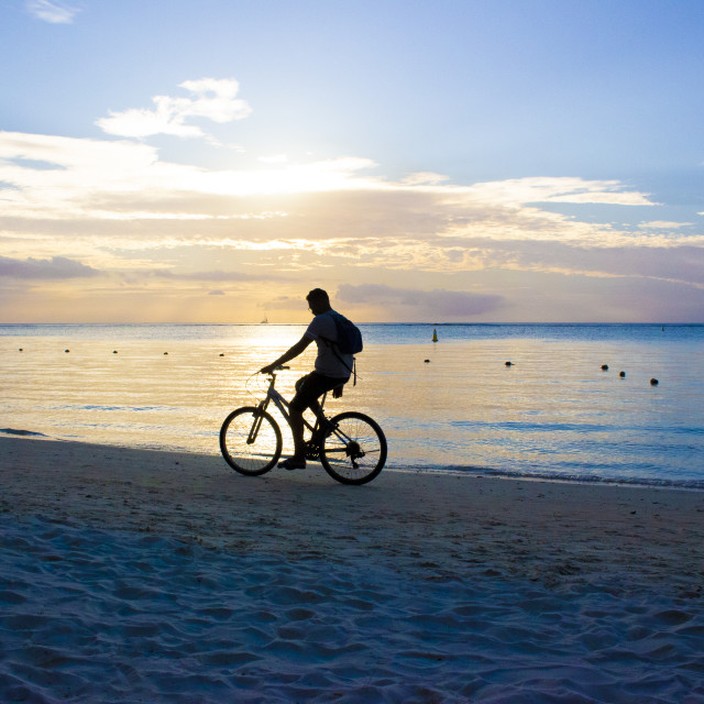 """Boy riding a bike on Troux aux Biches Beach, Mauritius"" stock image"