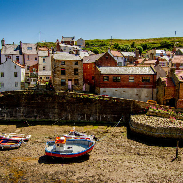 """Moored Fishing Boats in Staithes Beck, Cottages to the Background. Staithes, Yorkshire, England."" stock image"