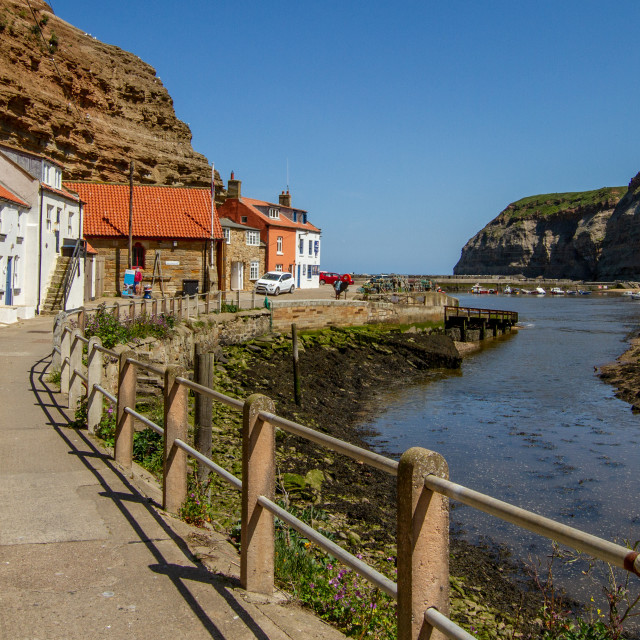 """View along Staithes Beck towards North Side Cottages, Cowbar Nab and the Harbour. Yorkshire, England."" stock image"