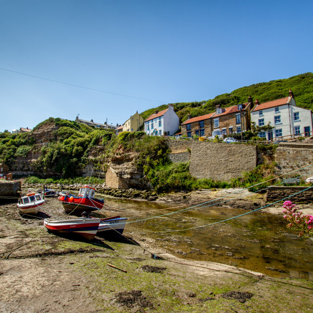 """Fishing Cobbles Moored in Staithes Beck, Fishermens Cottages in the Background. Staithes, Yorkshire, UK."" stock image"