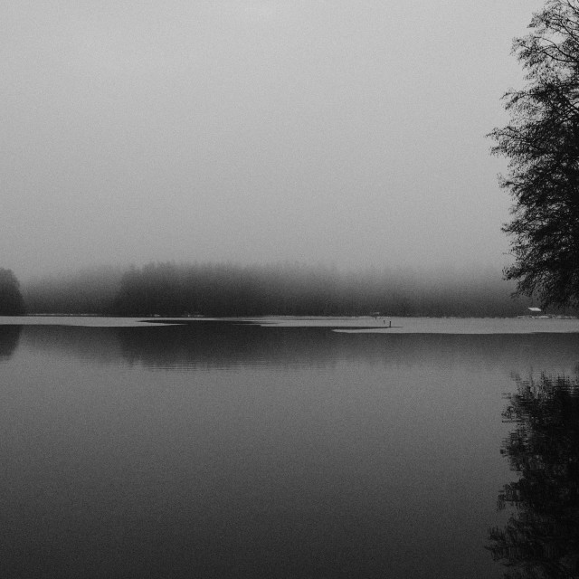 """Misty winter lake reflections in black and white"" stock image"
