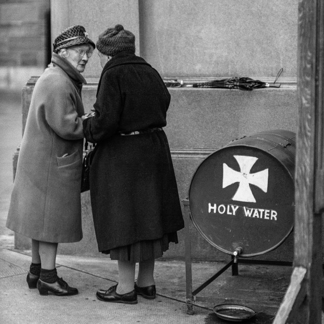 """""""Two old ladies chat while collecting holy water from a barrel be"""" stock image"""