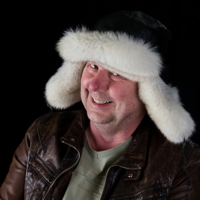 """Man in leather jacket and earflap hat"" stock image"