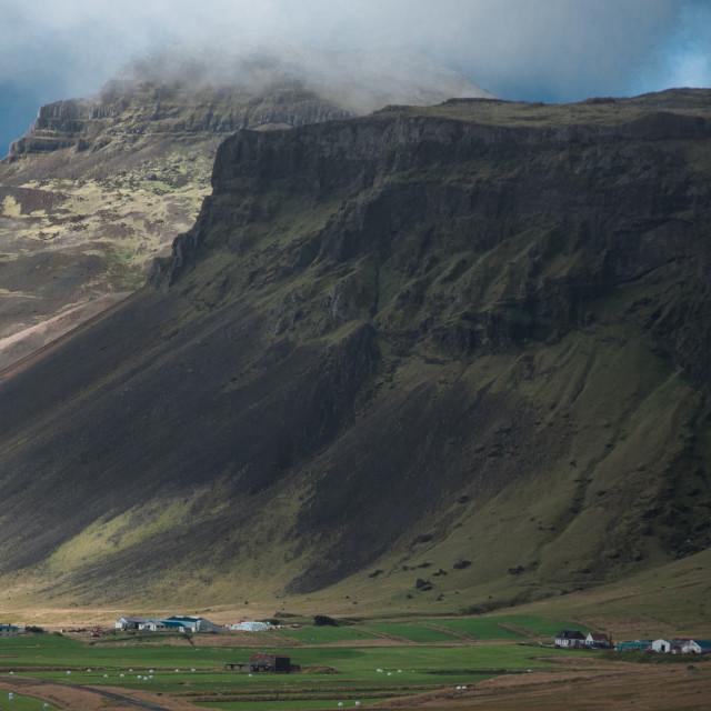 """Farmhouses huddle beneath steep mountainsides near Breidavik val"" stock image"