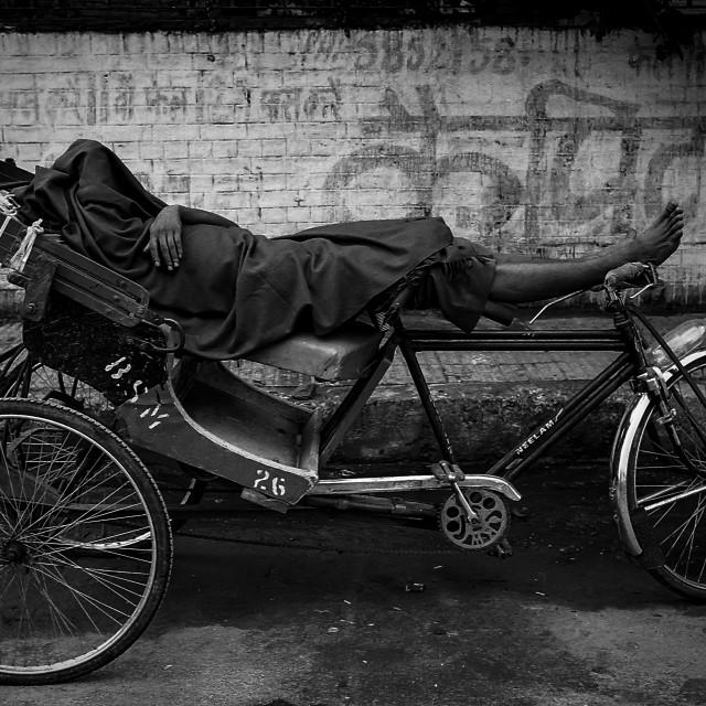 """Sleeping Rickshaw Cyclist, N. Delhi, India"" stock image"