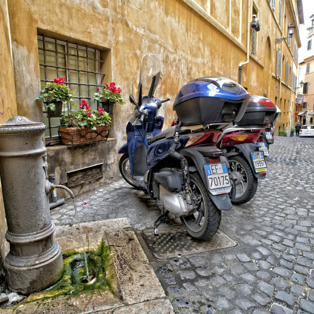 """Scooters parked on a cobbled street in Rome"" stock image"
