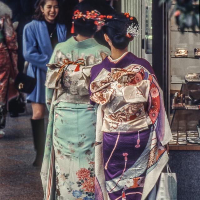 """Two Japanese women wearing full kimonos in busy shopping street"" stock image"