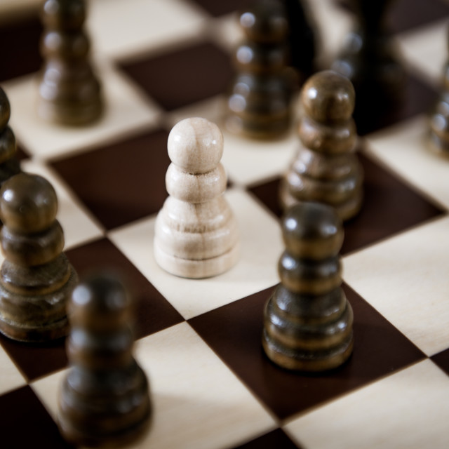 """""""White chess pawn surrounded by black pieces concept of racial gr"""" stock image"""