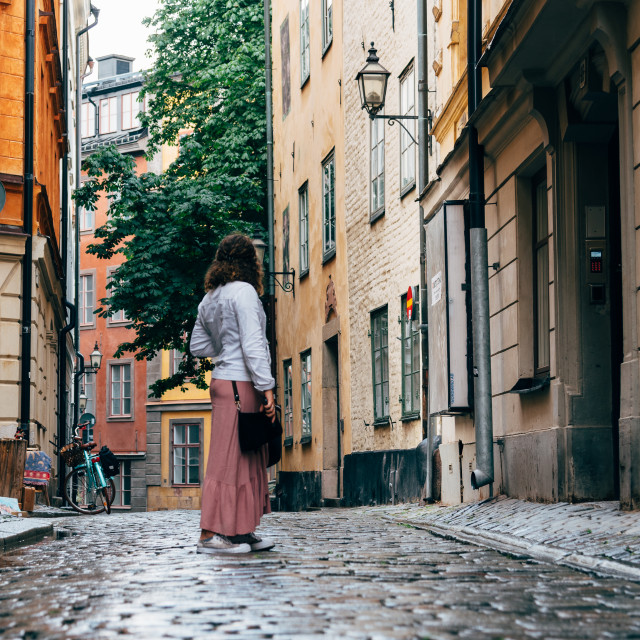 """Beautiful young woman is looking back in a picturesque and narrow cobblestoned street"" stock image"