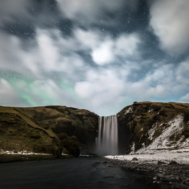 """""""Skogafoss with faint northern lights above clouds"""" stock image"""
