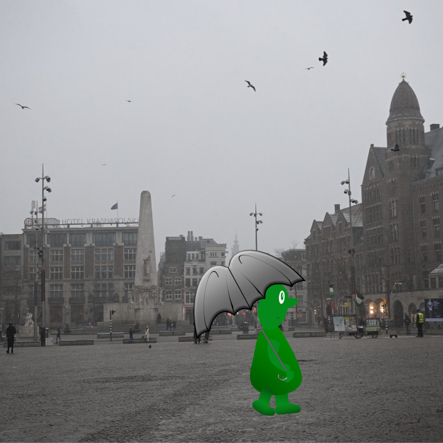 """""""Amsterdam The Netherlands Little green man walking across the Dam in a snow storm. Animation available"""" stock image"""