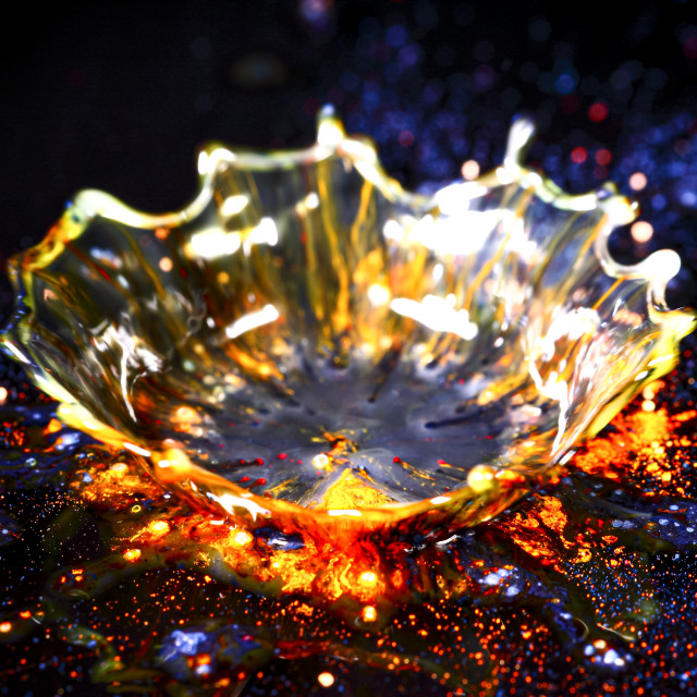 """""""Drops of water colliding with powdered dye to create a multi coloured abstract droplet collision"""" stock image"""