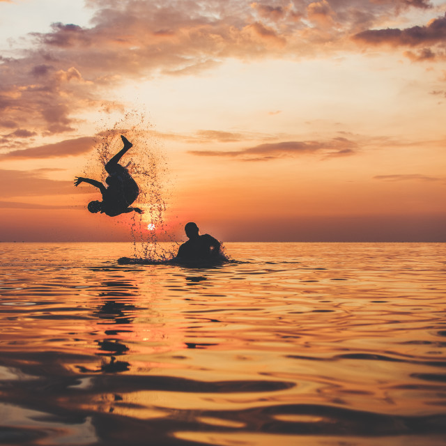 """""""Boys are playing in the sea at the very end of the day. Jumping at the sunset enjoying summer and life."""" stock image"""