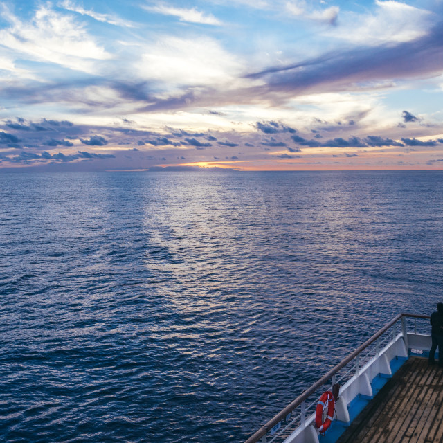 """""""Couple enjoying sunset at open sea from the back of a cruise ship"""" stock image"""