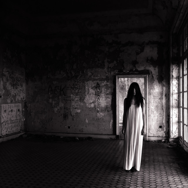"""""""""""Hiding From The Truth"""" - Woman in long dress standing in an abandoned building"""" stock image"""