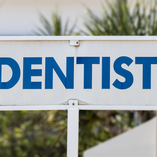 """""""Dentist sign outside practitioner in bold blue and white"""" stock image"""